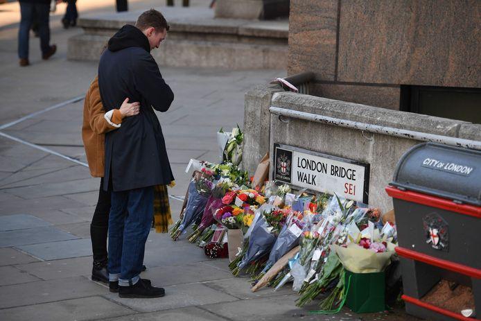 Mensen leggen bloemen om de slachtoffers te gedenken.
