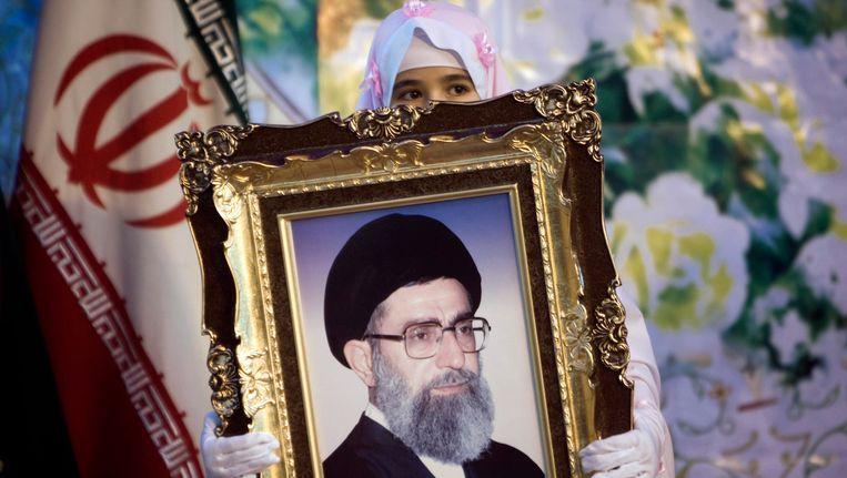 Een meisje houdt een foto van ayatollah Ali Khamenei vast. Beeld REUTERS