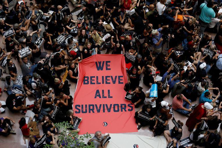 Activisten houden tijdens de zitting van Ford en Kavanaugh buiten een spandoek omhoog waarop staat 'we geloven alle slachtoffers'.