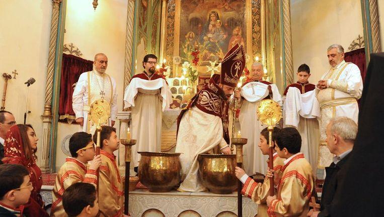 Een Armeens-orthodoxe priester leidt een dienst ter ere van het Armeense Kerstfeest, 6 januari in de Syrische hoofdstad Damascus. Beeld afp