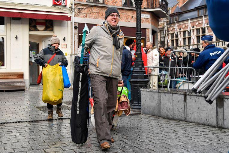 Gepakt en gezakt verlaten wachtenden de rij om de Grote Markt op te komen en hun polsbandje te krijgen.