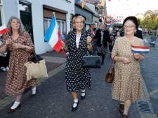 Met vlaggetjes zwaaien in de mode van toen tijdens Vrijheidstocht in Axel