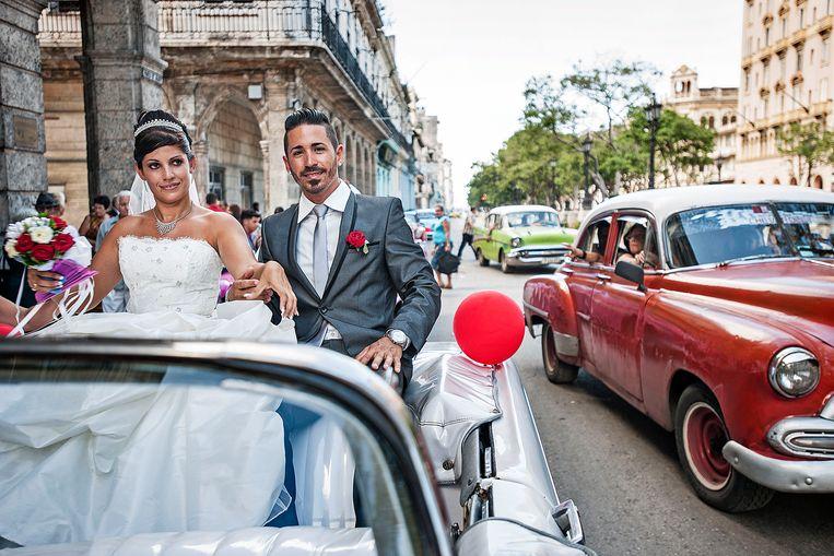 Een Cubaans echtpaar stapt in een oldtimer om hun huwelijk te gaan vieren. Beeld Guus Dubbelman