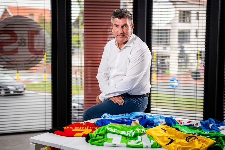 Patrick De Koster, poserend bij shirts van Kevin De Bruyne.
