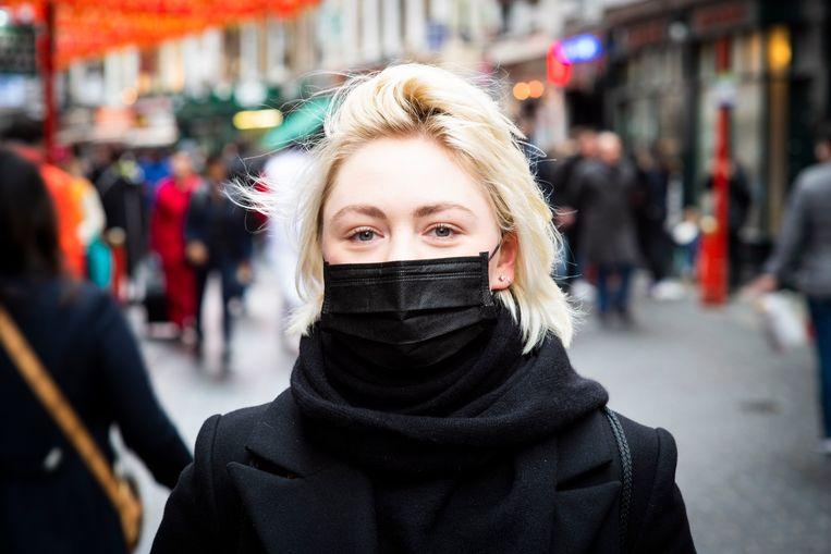 Een meisje draagt een mondmasker.