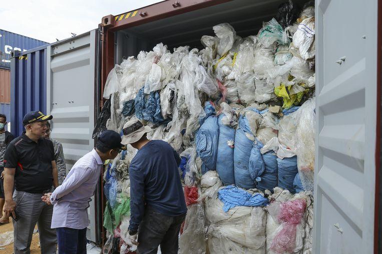 Indonesische douanebeambten checken een container vol geïmporteerd plastic.  Beeld AFP
