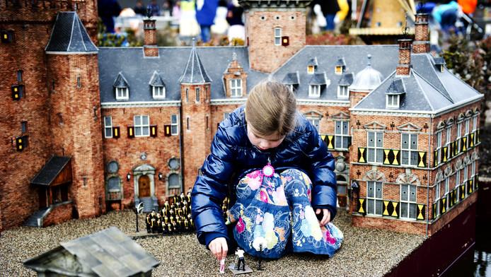 Een jonge bezoeker speelt met een miniatuurpop in het vernieuwde Madurodam in Den Haag.
