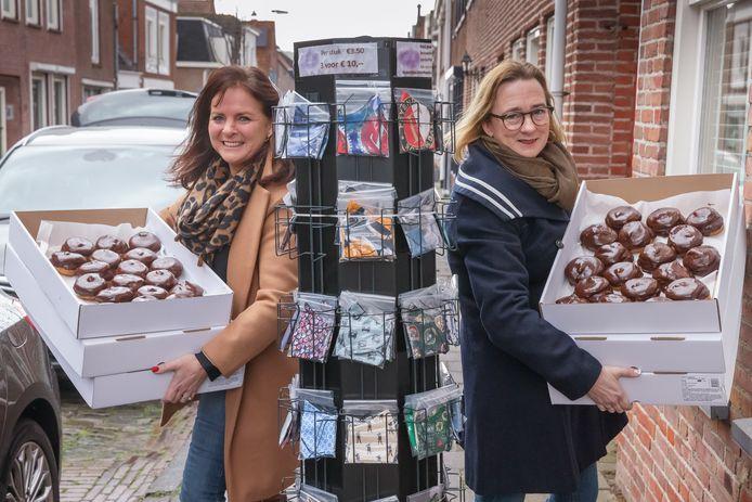 Hadewych den Ridder (links) en Pauline Joosten hebben groot succes geboekt met Moerdijkse Mondkapjes. De opbrengst is bestemd voor ouderen. Ze deelden vorige week donderdag 500 bossche bollen uit.