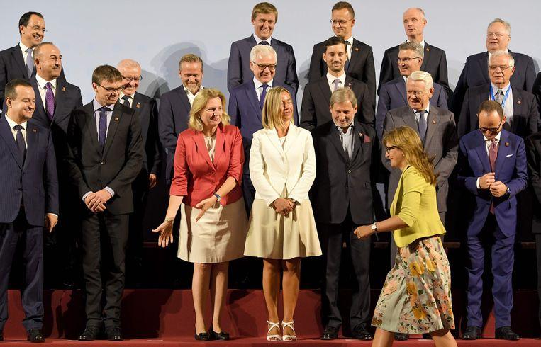 Gastvrouw Karin Kneissl, in het oranje jasje, ontvangt haar Europese collega-ministers van Buitenlandse Zaken in Wenen. Beeld Roland Schlager / AFP