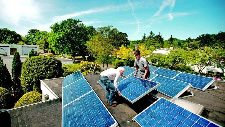Trouw-redacteur Vincent Dekker (links) plaatst samen met de loodgieter twaalf zonnepanelen op zijn dak. Foto: Olaf Kraak Beeld