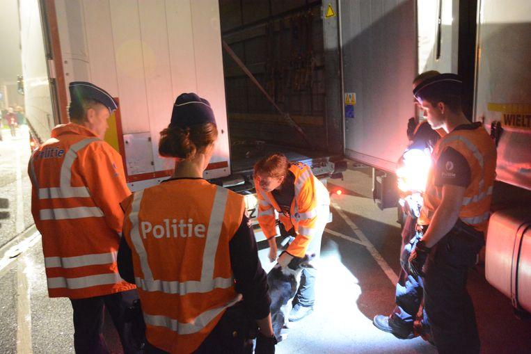 Een politieactie waarbij vrachtwagens worden onderzocht op mogelijke verstekelingen in Kruibeke.