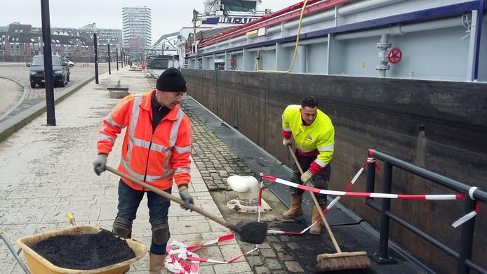 Elbert Moed en Henk Baum (rechts) van aannemersbedrijf Weijers repareren de 'hoogwaterschade' op de  Waalkade.