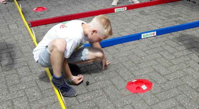 Een deelnemer aan het Nederlands kampioenschap knikkeren probeert een knikker in de pot te schuiven.