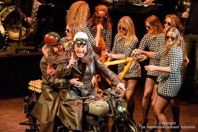 Henk Weusthof rijdt met een motor het podium op tijdens de revue van de SNOR.