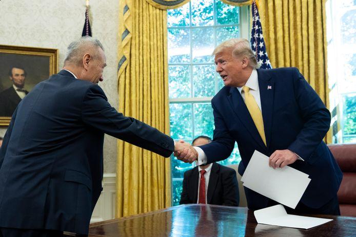 De Chinese vicepremier Liu He (links) en de Amerikaanse president Donald Trump schudden elkaar de hand in het Oval Office van het Witte Huis na afloop van het tweedaagse handelsoverleg.