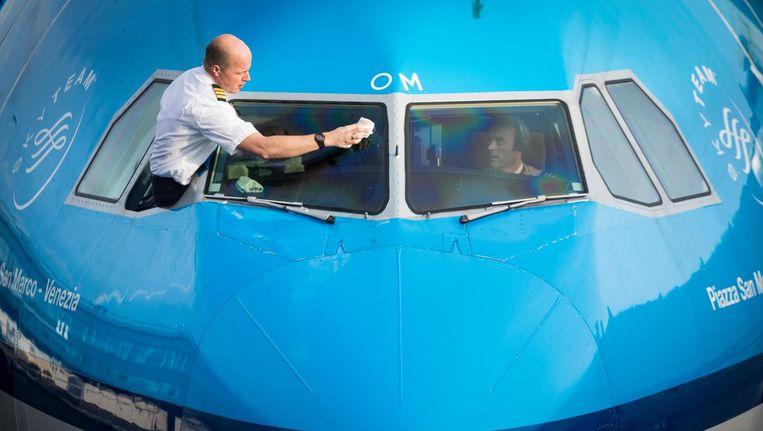 Een KLM-piloot maakt de voorruit van de cockpit schoon. Beeld null
