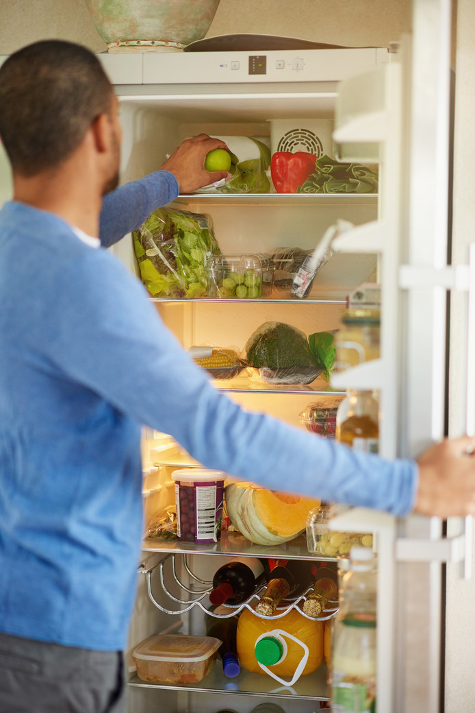 Rearview shot of a man opening a fridge filled with healthy food at home