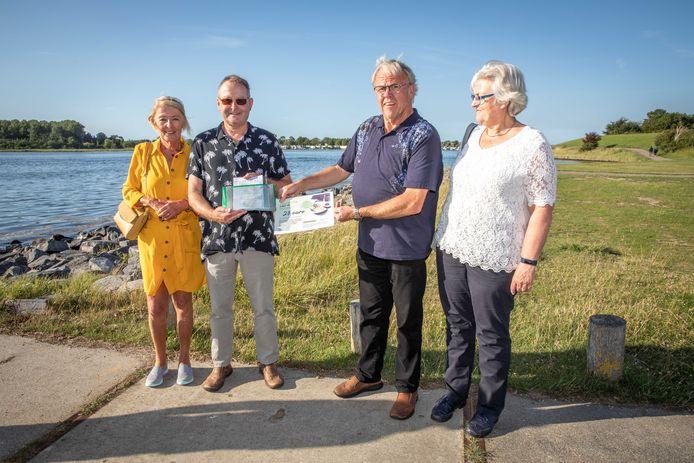Ineke en Rinus Nederveen (links), al meer dan veertig jaar vaste gast op camping De Haas, krijgen hun cadeaubon van de campingeigenaren Piet en Joke Verburg.