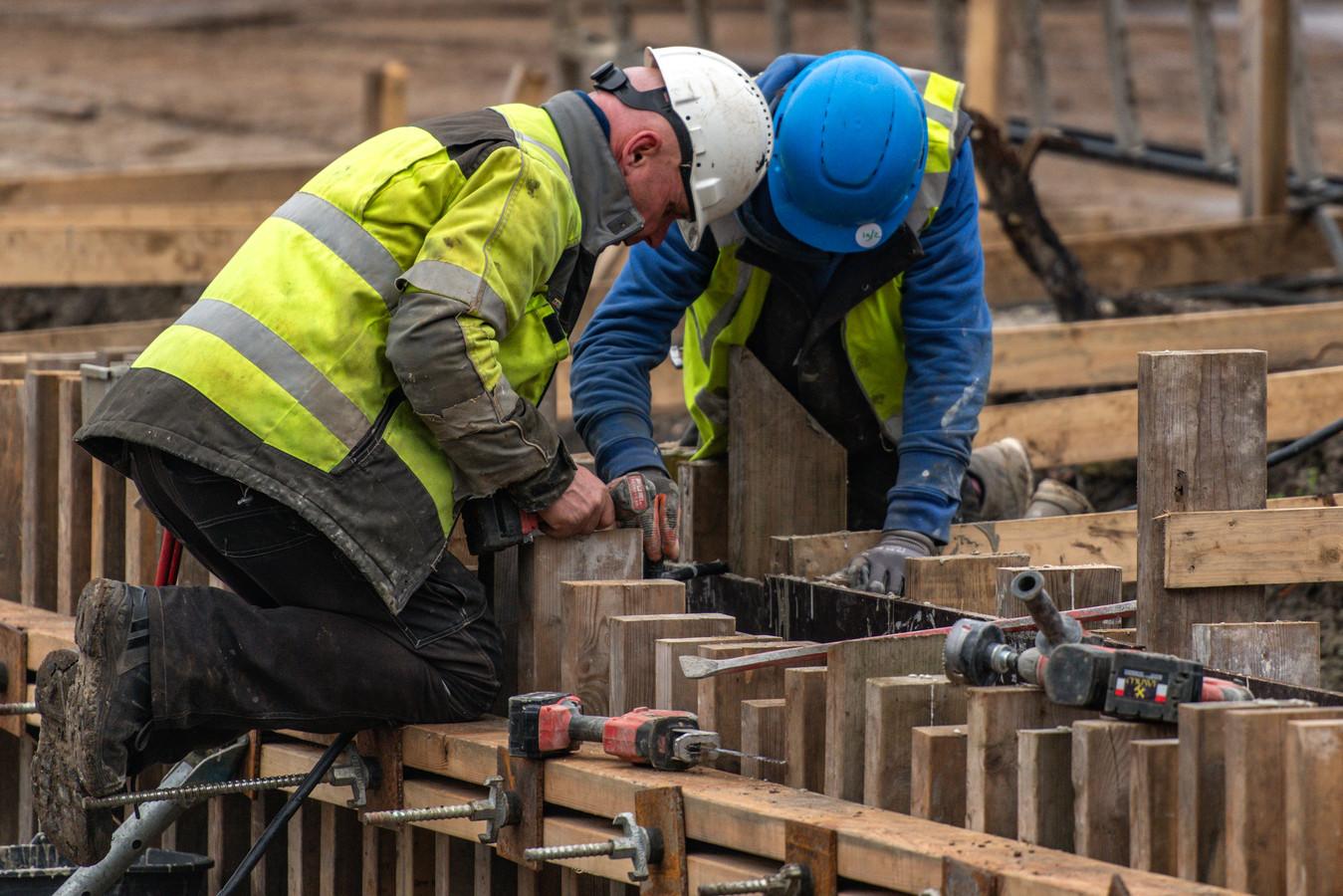 Twee bouwvakkers aan het werk op een bouwplaats.