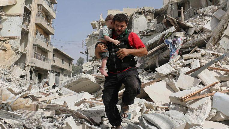 Een Syrische hulpmedewerker draagt een baby weg van een ingestort gebouw in de wijk Qatarji in Aleppo. Beeld afp