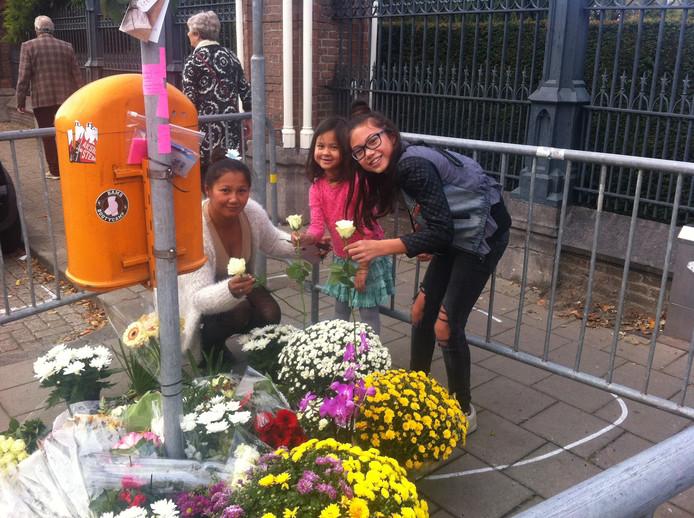 Winny Hoogervorst en haar dochters Ziggy-Mae (11) en Coco-Guillana (5) leggen ieder een witte roos.