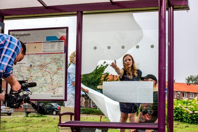 Melissa Vermeule geeft aanwijzingen bij het beplakken van het bushokje aan het Oranjeplein.