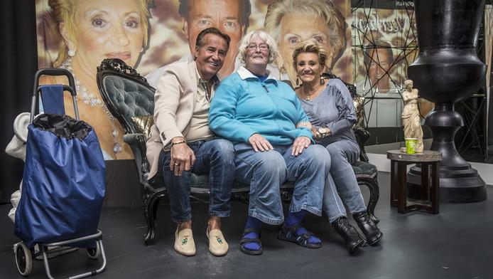 Fan Jopie Steinbruckner (m) met Ton en Hanny Veerkamp. Haar wagentje zit vol Man bijt hond-prullaria.