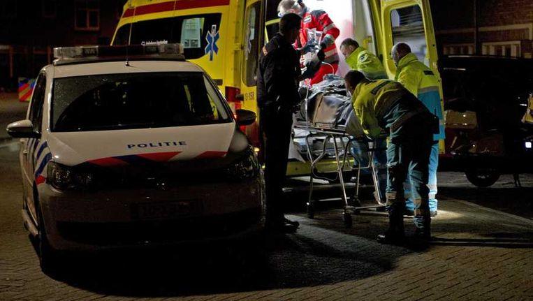 Een zwaargewonde man wordt in de Van Bossestraat in de Amsterdamse Staatsliedenbuurt in een ambulance geholpen. Beeld anp