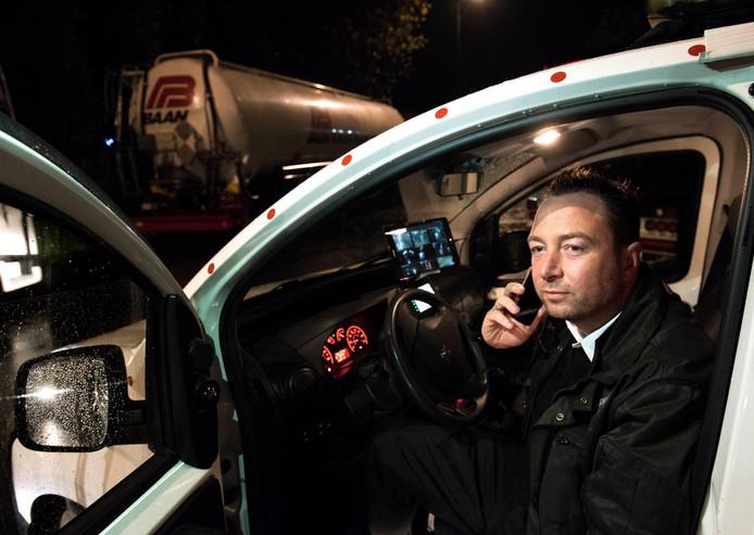 Martijn van Duin houdt vanuit de auto camerabeelden en daarmee het hele bedrijfsterrein van Mijdrecht in de gaten.