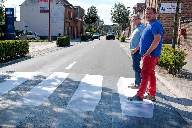 Schepen Wim Mombaerts en burgemeester Kurt Ryon testen het 3D-zebrapad uit.