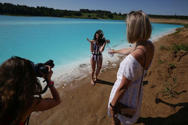 Een jonge vrouw poseert bij het meer, dat gebruikt wordt als afvaldump voor de lokale energiecentrale.  Beeld AFP