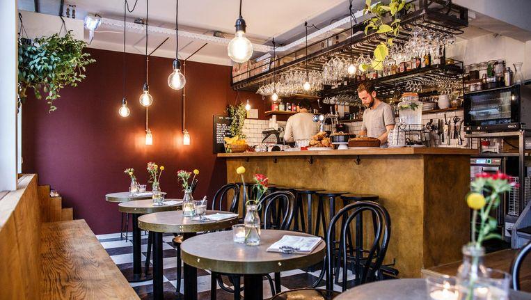 Gedempte lichtbollen, rood pleisterwerk en een door Grevelink en Kolkman gemetselde muur geven het café een zachte uitstraling Beeld Carly Wollaert