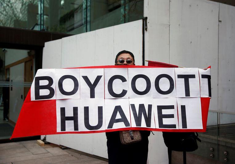 Een demonstrant betoogt voor de rechtbank in Vancouver voor de uitlevering van Huawei-topvrouw Meng Wanzhou en voor strafmaatregelen tegen het Chinese bedrijf.  Beeld null