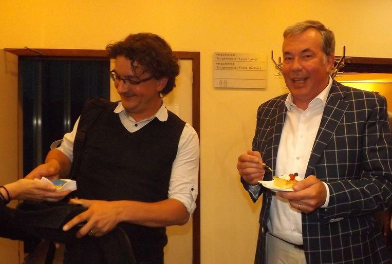 Schepen Dany Bosteels (rechts) geniet van zijn stuk taart. Raadslid Sven Cools neemt een portie in ontvangst.