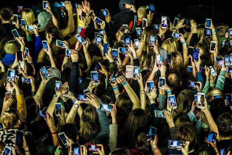 De beleving tijdens een concert anno 2018. Honderden telefoons gaan de lucht in voor opname wanneer Lil'Kleine het podium betreedt. Beeld anp