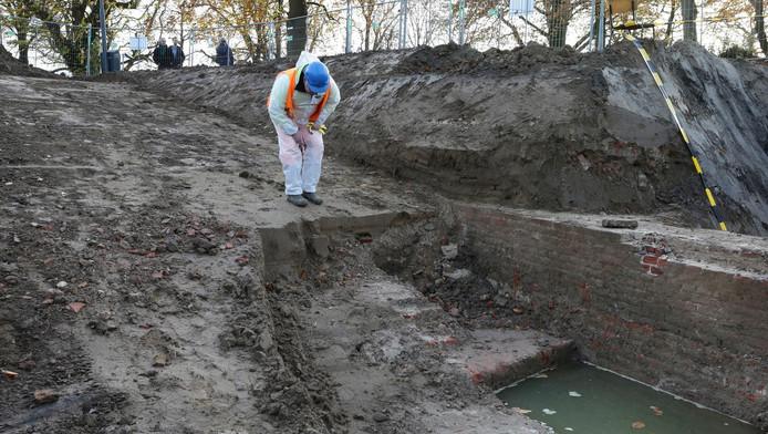 Een archeoloog bij de gevonden stadsmuur.