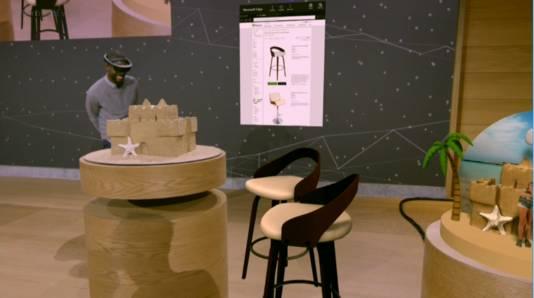 Het beeld door de bril van een medewerker van Microsoft. Hij projecteert tekeningen van krukken naar zijn tafel om te zien hoe het geheel eruit ziet.