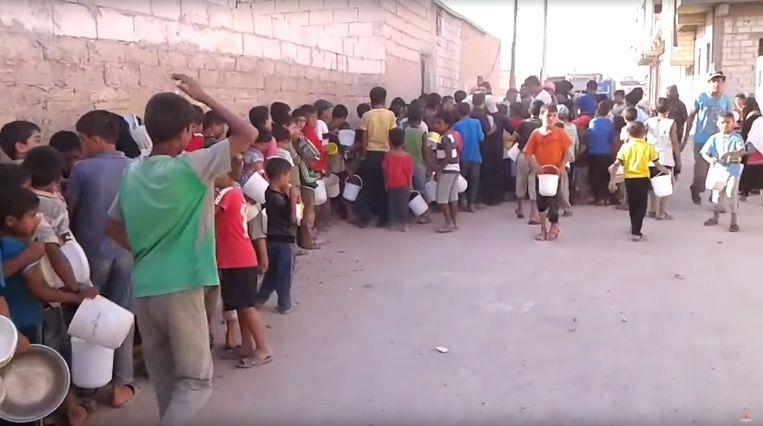 Beeld van video op de website van Raqqa is Being Slaughtered Silently. Rijen kinderen die op de tweede dag van de ramadan bij de gaarkeukens staan te wachten op eten. Beeld .