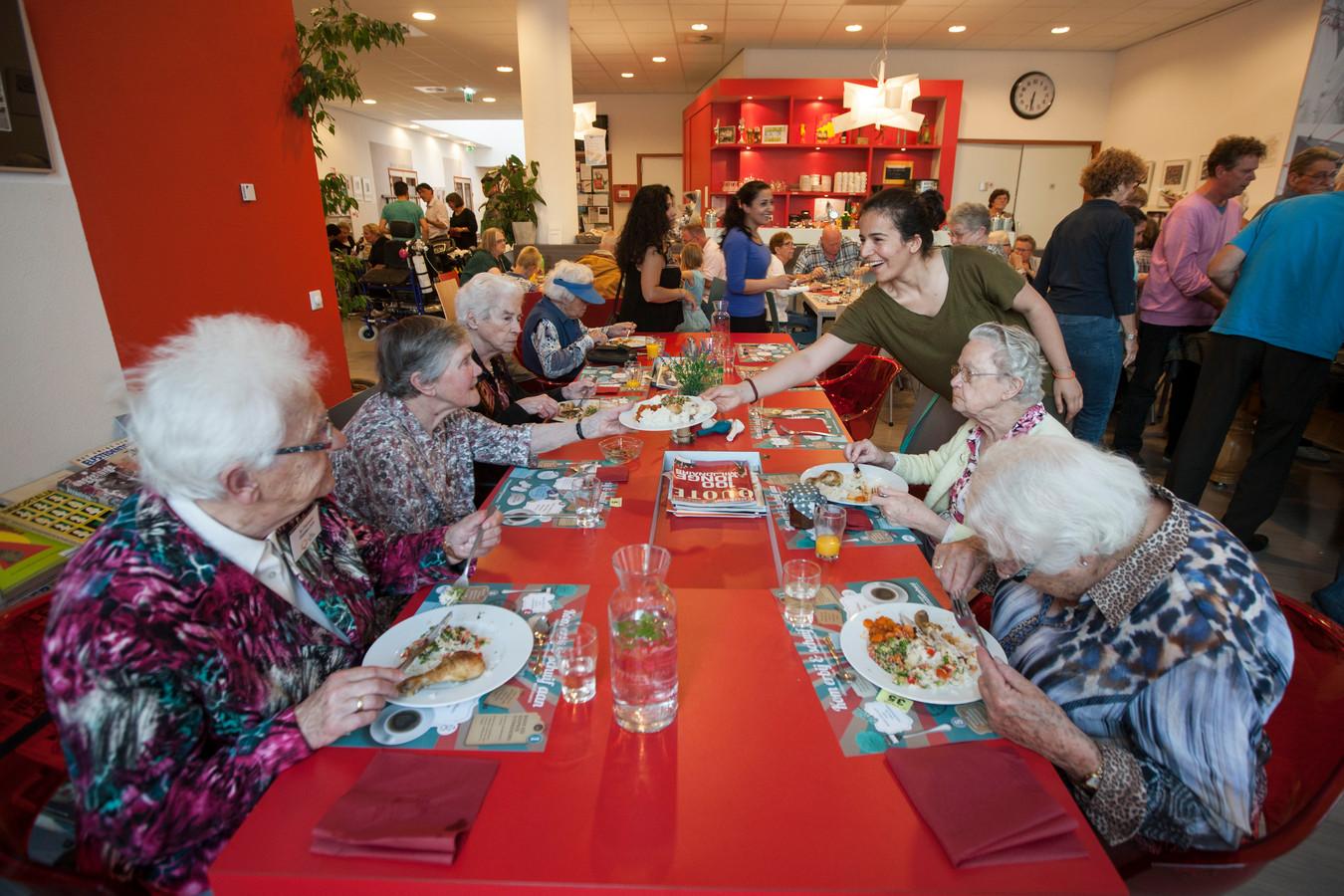 Archiefbeeld: De Syrische Nouran Breem geeft een bord met eten aan in wijkcentrum Waterkracht.  Negentig mensen schoven aan de Tafel van Samen in Waterkracht in Zutphen aan. Syrische koks bereidden samen met Nederlandse vrijwilligers het diner voor alle gasten.