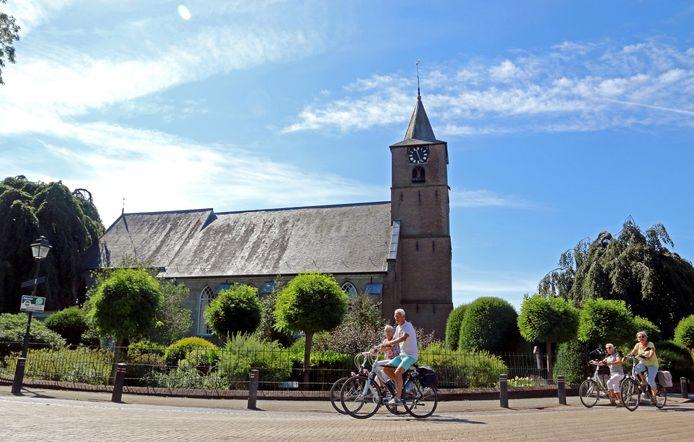Fietsers passeren voor de Hervormde Kerk van Echteld, in het hart van de Betuwe.