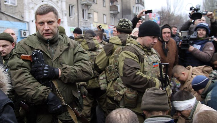 Rebellenleider Aleksander Zachartsjenko (l) naast een aantal gevangengenomen Oekraïense militairen. Zij waren de verdedigers van het vliegveld van Donetsk en werden gisteren door de stad geparadeerd, waarbij ze werden geslagen, bespuugd en uitgescholden. Beeld afp