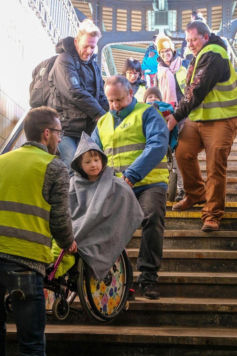 De treinbestuurders dragen de kindjes in hun rolstoel van de perrontrappen af.