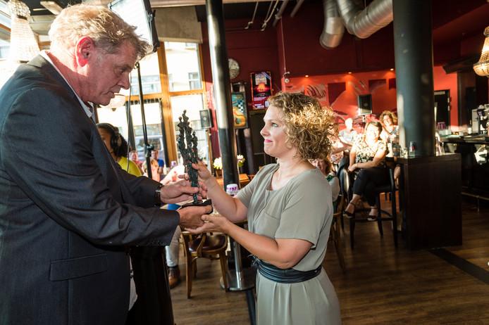 Presentator Gerard Smink van Hengeloos Peil, het politieke café van deze krant en Radio Hengelo TV, reikt de persprijs uit aan Esther van Spall van Wijkracht.