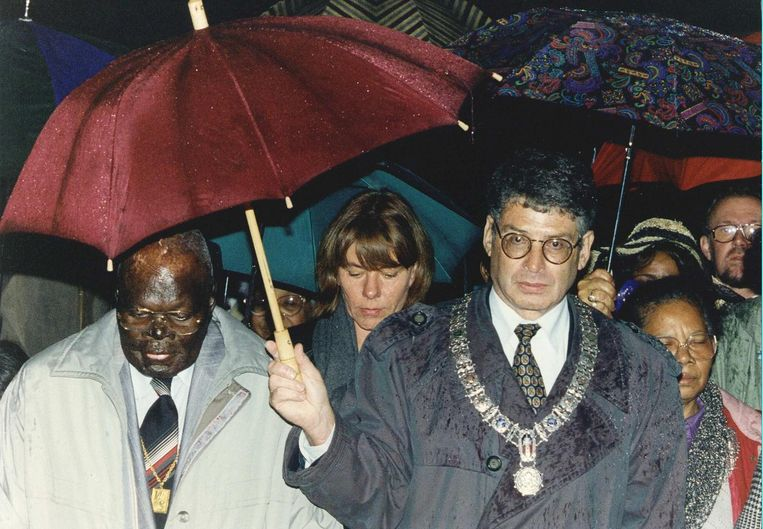 1993: Burgemeester Ed van Thijn houdt tijdens de eerste herdenking een paraplu boven Pa Sem, alias Willem Symor, die gewond raakte tijdens het redden van twee kinderen bij de ramp in de Bijlmer. Beeld ANP