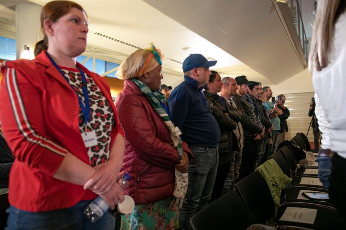 Oud-deelnemers aan het Tilburgse werklozenproject tijdens de minuut stilte in de raadszaal voor de overleden slachtoffers.
