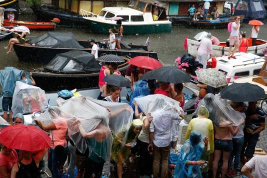 Toeschouwers schuilen onder paraplus tijdens de Canal Parade van de Gay Pride