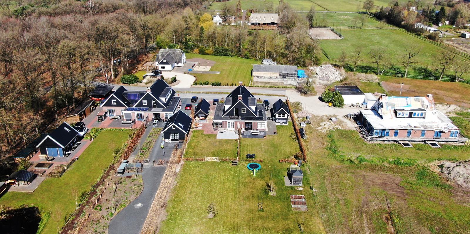 Het plattelandsbuurtje in Uddel dat al tijden op stelten staat. Niet alleen het huis waarop een bouwstop rust (rechts) moet van de gemeente Apeldoorn worden gesloopt, ook moet de linkerhelft van de linker dubbel 2,5 meter verschuiven.