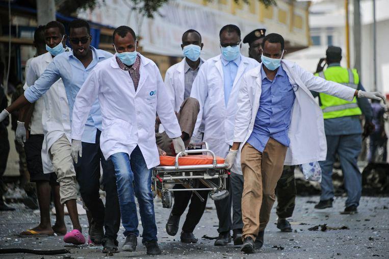 Eerstehulpverleners dragen het lichaam van een van de slachtoffers weg.