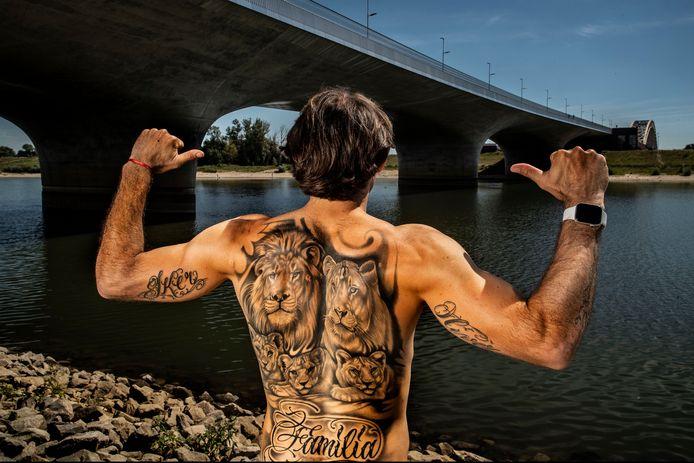 Edgar Barreto bij de Waalbrug met zijn tattoo's. De leeuwen symboliseren hemzelf, zijn vrouw en drie zonen Matias, Iker en Oliver.
