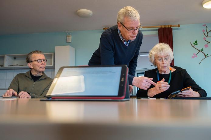 Ouderen krijgen van een lid van het Gilde de Baronie uitleg over de werking van hun smartphone.
